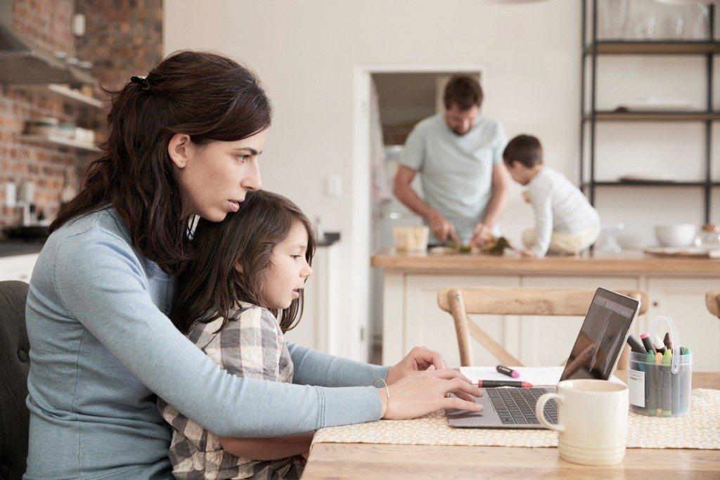 Madre trabajando en casa con un niño en su regazo.